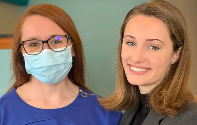 Two women smiling one with mask on